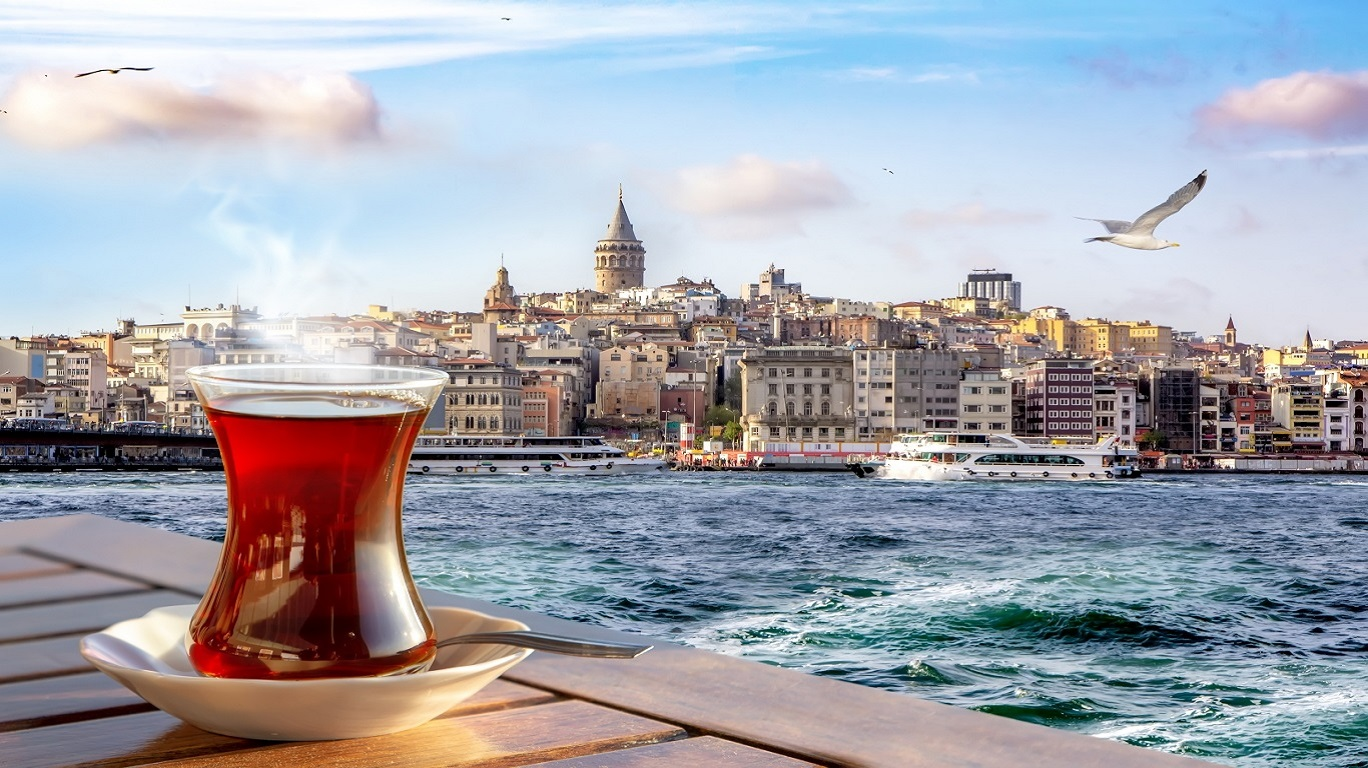 a cup of turkish tea in a traditional glass against the background of the golden horn and the galata tower in istanbul